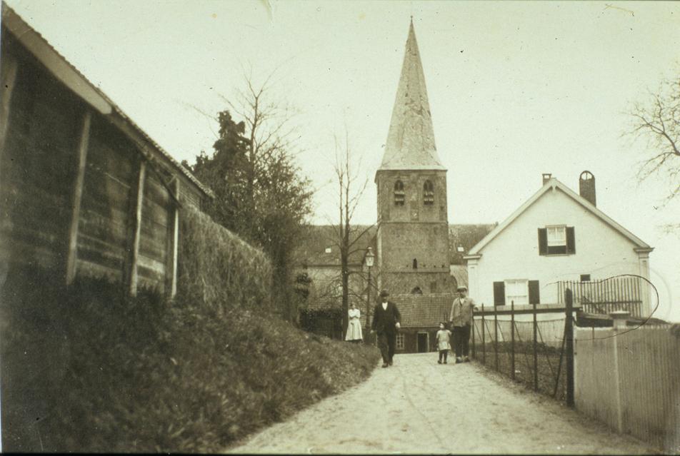 """Het Kerkpad onmiddellijk achter de Oude Kerk. De schuur die voor de toren staat herbergde ooit de werkplaats van de timmerman D. Klaassen die tevens vanaf 1872 uitbater van het hotel """"de Doornenkamp""""was."""