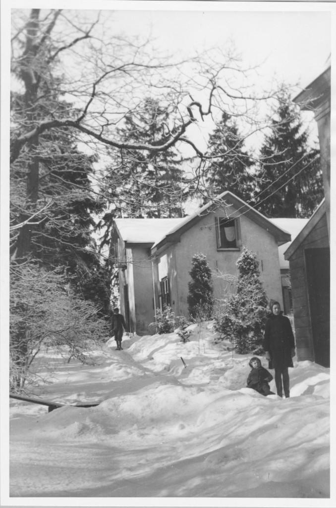 De koetsierswoning met links een deel van het oude koetshuis. De kinderen Verschoor in de sneeuw met op de achtergrond hun vader, aanvankelijk chauffeur later concierge van het huis.