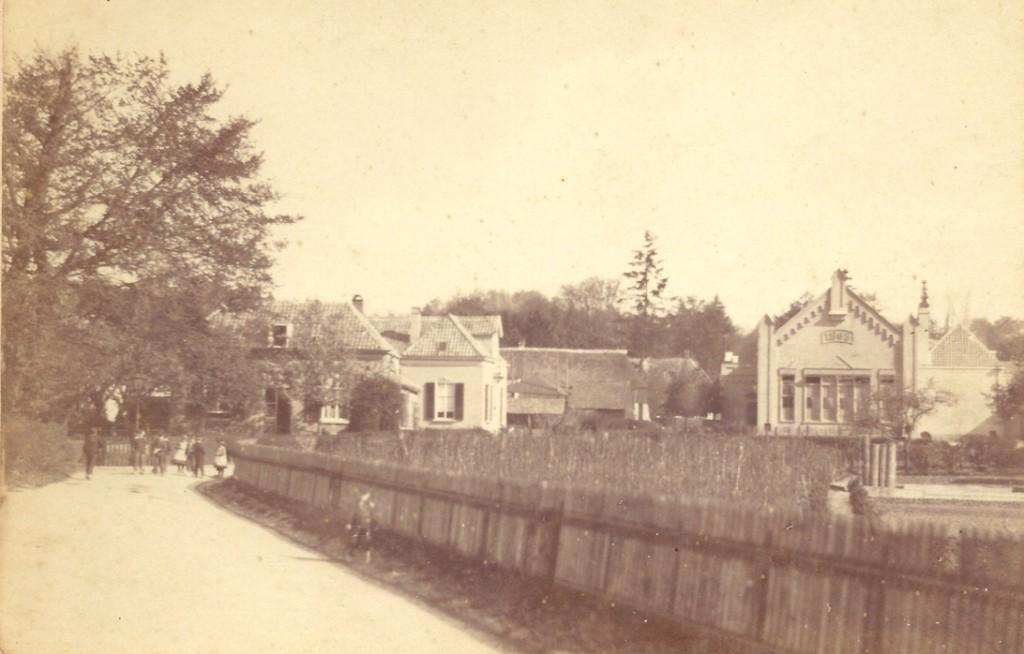 """Een foto van rond 1890 met links, onder de boom, de ingang van de """"Nattesteeg"""", de huidige """"Rozensteeg"""". Het pad liep voor de Concertzaal langs over de """"Eng"""" naar de Kneppelhoutweg. Het stuk over de """"Eng"""" en daarna heet nu """"Rozenpad"""". Rechts van her oorspronkelijke gebouw (onder het zadeldak) de oostelijk aangebouwde lokalen en rechts daar weer van de dienstwoning van de hoofdonderwijzer Aart van Ewijk."""