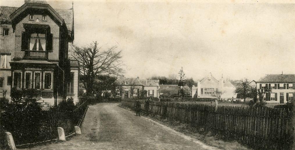 """De boerderij van De Graas is zichtbaar op een foto genomen vanaf de hoek Weverstraat/ Benedendorpsweg. Links vooraan de villa die rond 1900 werd bewoond door mr. J. A. van Hoek. Na zijn overlijden woonden zijn weduwe en tot 1944 zijn dochter H. A. van Hoek er. In 1944 ging de villa verloren. Rechts van de boom de manufacturenzaak van W. Klaassen Ezn. Dan het nog bestaande pand op huidig nummer 177-179, met daarnaast de boerderij van De Graas. Rechts daarvan aan de overzijde van de Weverstraat de Openbare Lagere School I (de """"Klompenschool"""") die in 1863 werd gebouwd en Aart van Ewijk als eerste hoofdonderwijzer kreeg. Deze woonde tot 1904 in de dienstwoning rechts van de school. Uiterst rechts """"De Meihof"""" van D.J. van der Ven. In het begin van de vorige eeuw heeft in de villa enige tijd de schilder Willem F. A. I.Vaarzon Morel gewoond."""