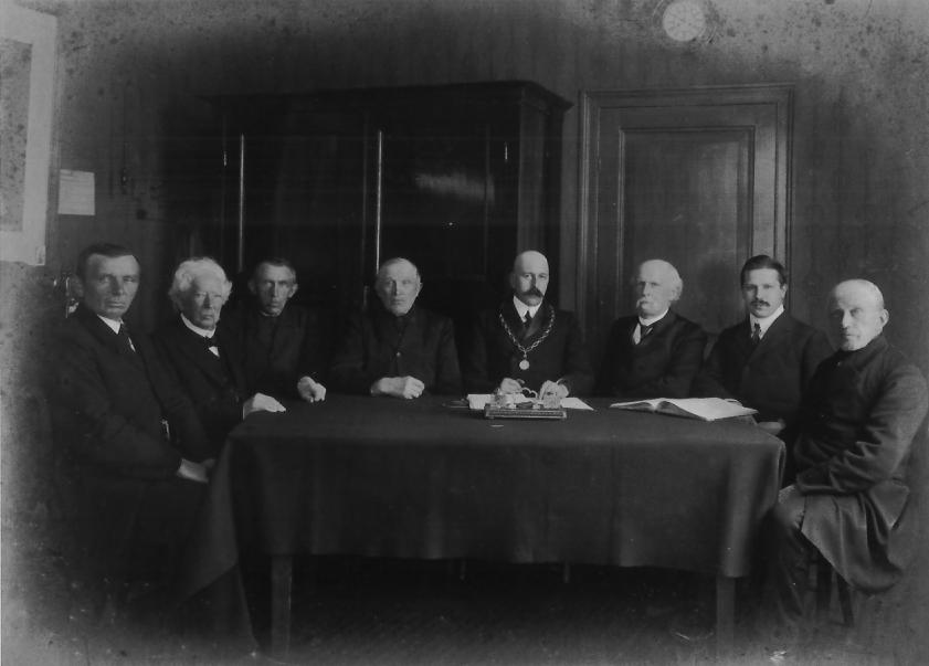 """De gemeenteraad van Doorwerth op 13 december 1910 bijeen in de """"De 2 Zalmen"""", met enige leden van de feestcommissie uit 1898. V.l.n.r.: R. Roosenboom, Baron Van Brakell, (bakker) Johannes van den Berg (bewoner het """"Stenenhuis""""""""), Jan van Maanen (boer op """"De Noordberg""""), burgemeester Jhr. Ferdinand Wttewael van Stoetwegen, gemeentesecretaris A.W.G. Rijnders, D.J. van de Garde, papierfabrikant Gerrit Schut."""