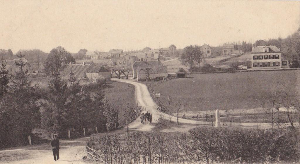 """Gezicht op Heelsum vanaf de kerkheuvel. Op de voorgrond de gedenkzuil Van Brakell, op de achtergrond rechts, gelegen aan de """"Aan de Beek"""", het in 1899 betrokken pand van de dameskostschool, het """"Huis Heelsum"""". In 1964 afgebroken om plaats te maken voor """"De Koningshof"""""""