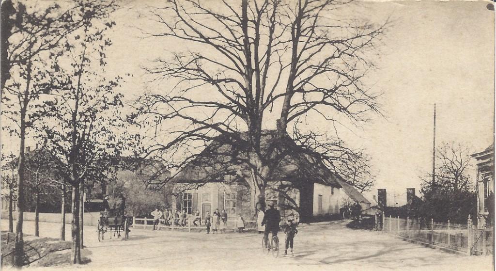 """De """"Oude Kosterie"""" met de lindeboom. Achter de kosterie het verhoogde erf waar de Oude Kerk stond. Ook aan de achterzijde van de kosterie het schoollokaal van meester Rennes. Rechts op de achtergrond de toegangspoort tot de begraafplaats die behoorde bij de oude R.K. kerk, later Hervormde kerk. Geheel links het bierhuis van Menting."""