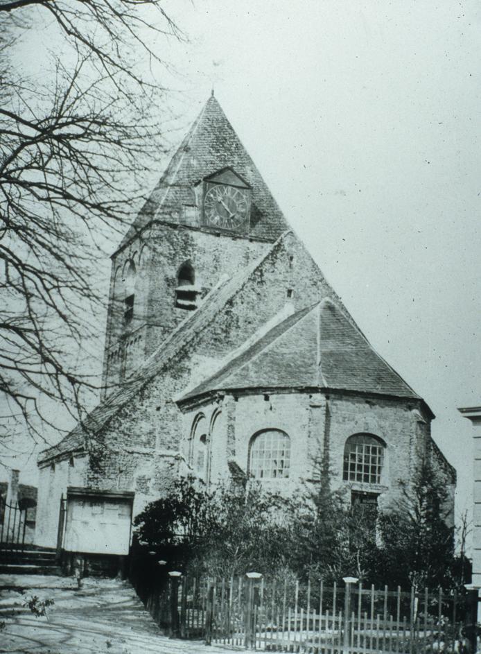 De Ned. Hervormde kerk met links het toegangshek tot de begraafplaats.