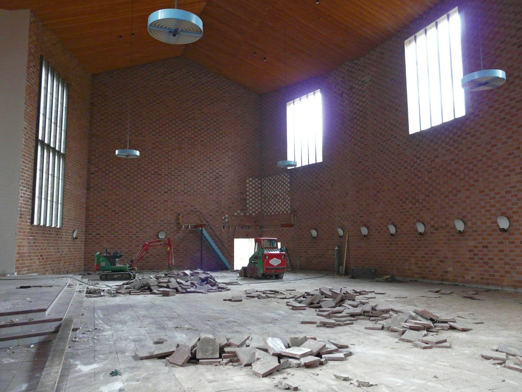 De voormalige kerkruimte van de Goede Herderkerk met rechts achterin de plek van het orgel. Op de wanden nog duidelijk zichtbaar de porisiostenen en de gipsbakjes t.b.v. de akoustiek.