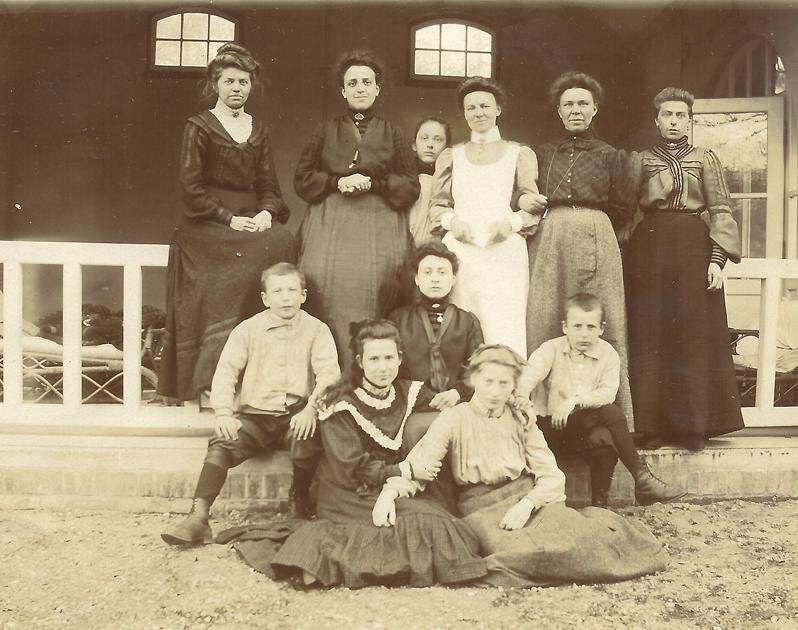 Enige leden van de familie Ruijtenberg met personeelsleden poserend voor een van de verandaas waarop de patienten de