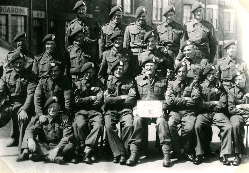 """Mannen van No 15 Platoon, D Company, 7th Battalion, The King's Own Scottish Borderers, poseren voor de fotograaf in Scarbourough, Engeland. Op de voorgrond, de man met het bord, de commandant: Lt. Kipping. Links naast hem Sgt George Nattras. Bovenste rij, derde van links, Pt. Ure; hij sneuvelde in """"the White House"""", Hotel Dreijeroord, te Oosterbeek"""