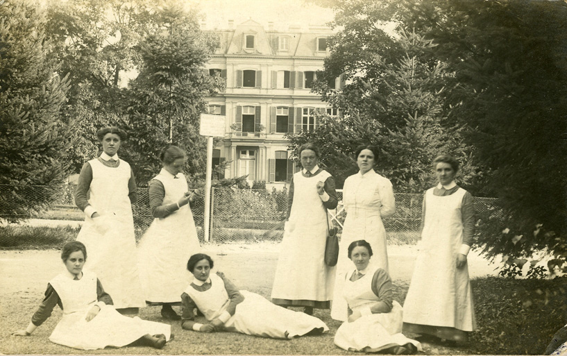 De directrice Tjassens poseert temidden van enige verpleegster voor het hoofdgebouw.